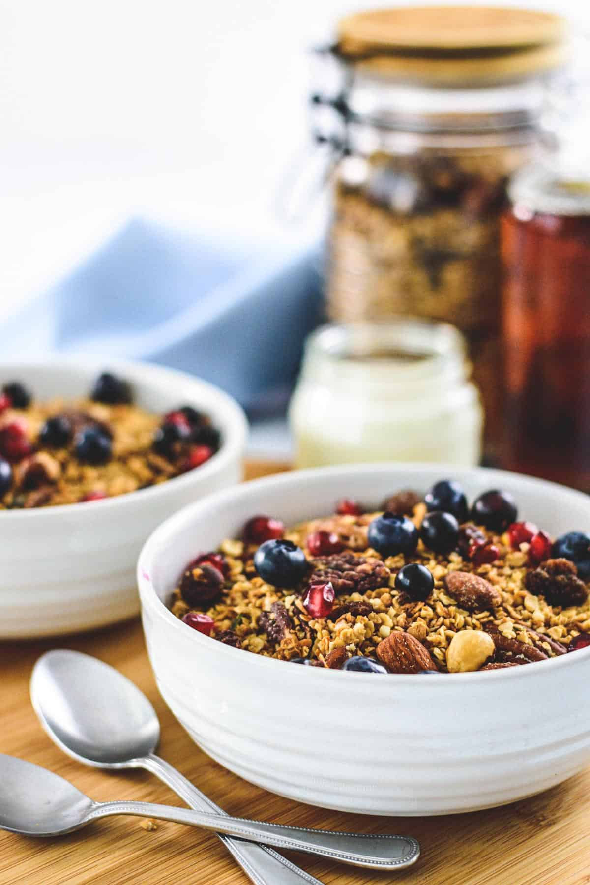 two bowls of granola with two spoons, milk and maple syrup
