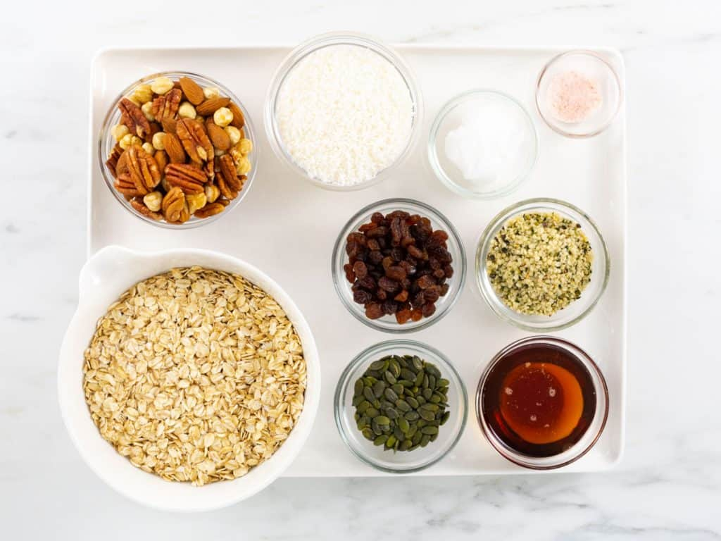 Granola ingredients - oats, coconut, nuts, hemp seeds, pumpkin seeds, maple syrup and raisins