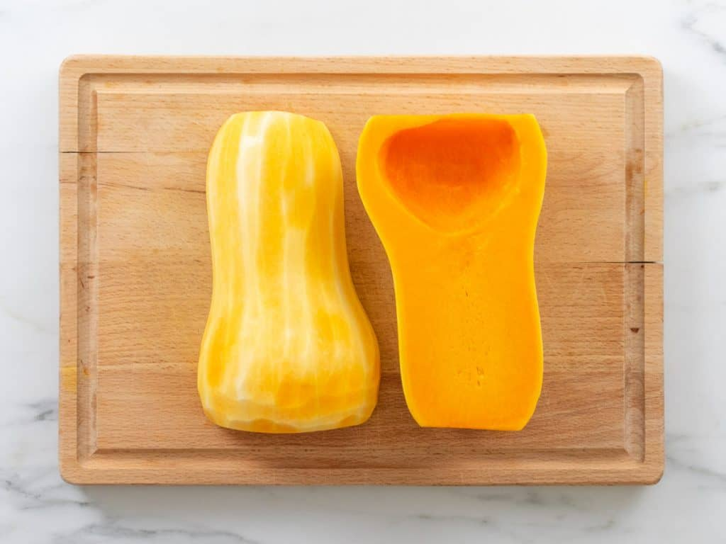 Peeled, halved and deseeded butternut squash on wooden chopping board