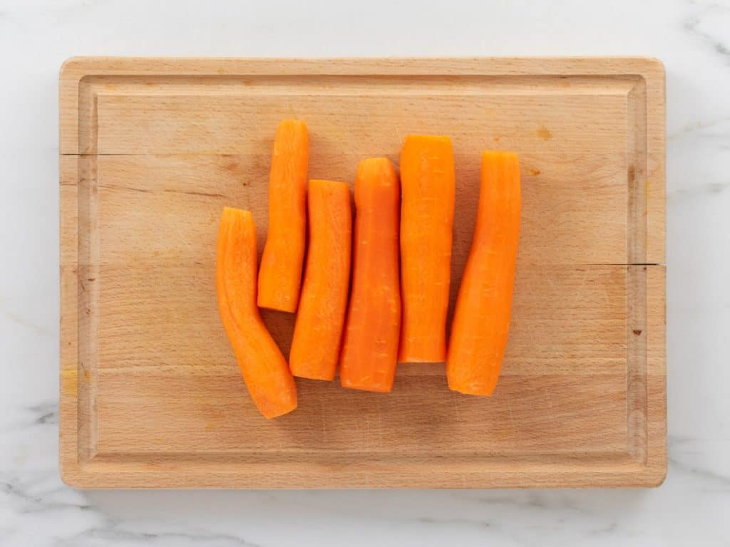 Six peeled and trimmed carrots on wooden chopping board