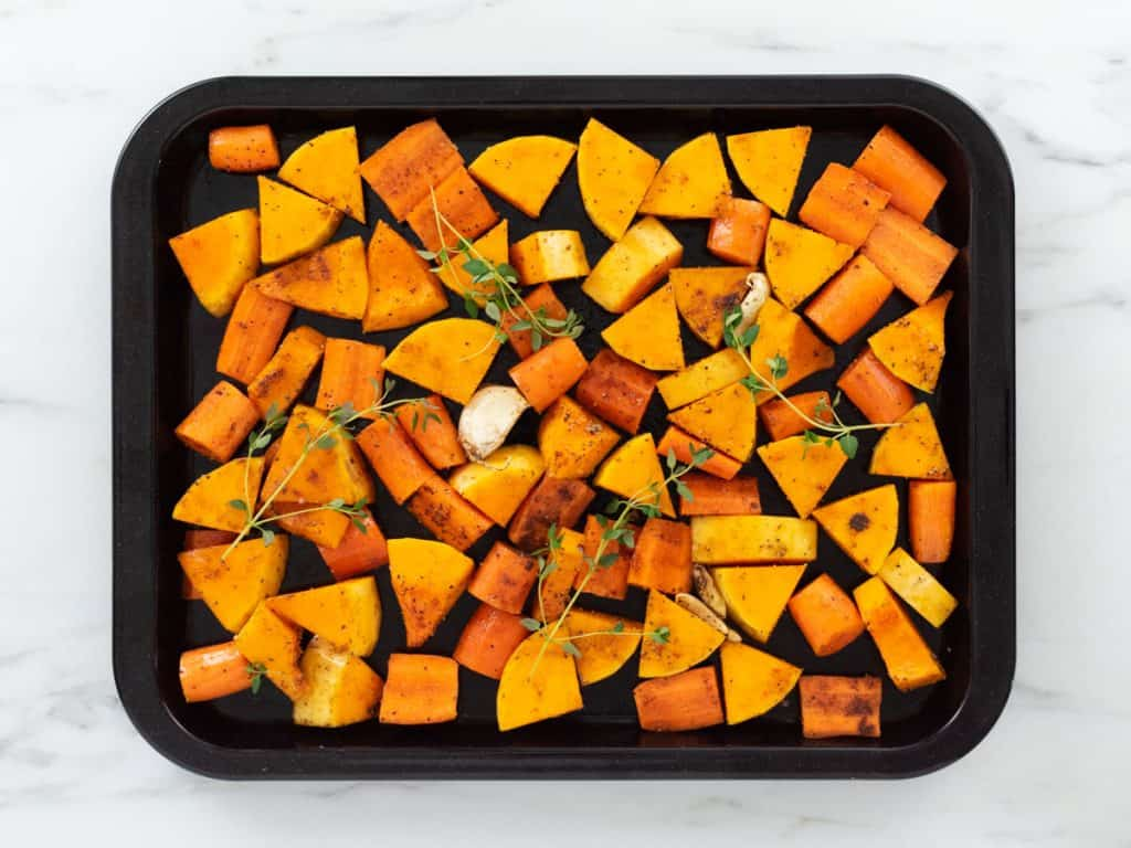 Chopped butternut squash and carrots on baking tray with fresh thyme, garlic and spices