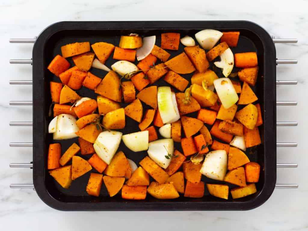 Baked butternut squash and carrots on baking tray with raw onions