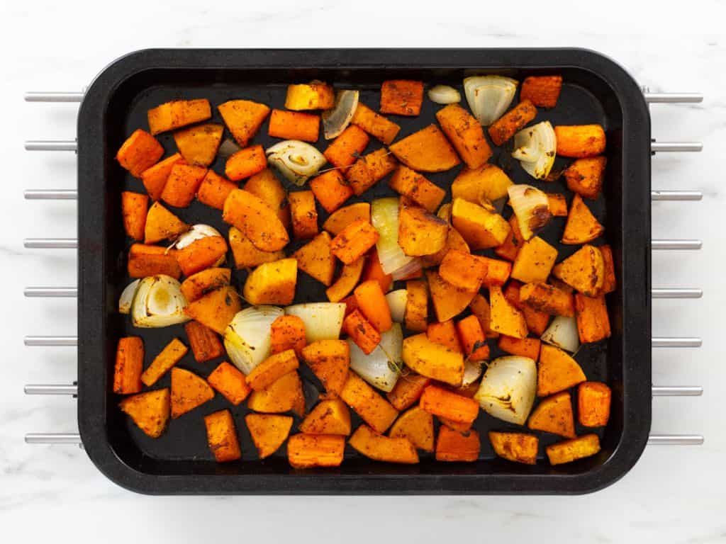 Roasted butternut squash, carrots, garlic and onions on baking tray