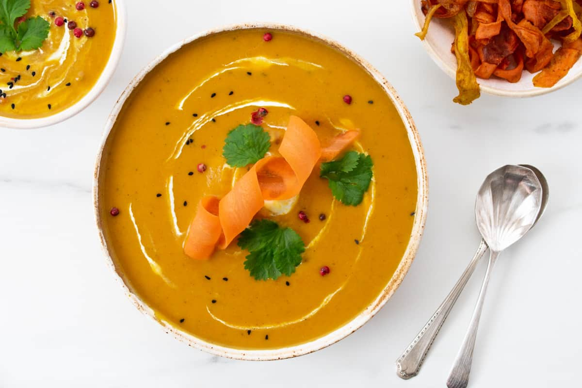 Butternut squash and carrot soup in large bowl with carrot and coriander garnish