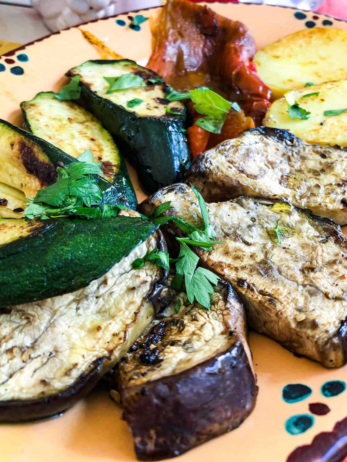 Oval platter with grilled courgette, red pepper, slices of aubergine and white potatoes
