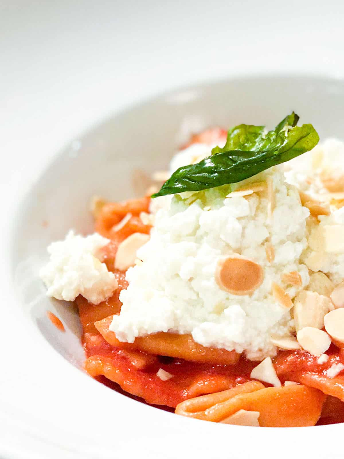 pasta in white bowl with ricotta and slithered almonds