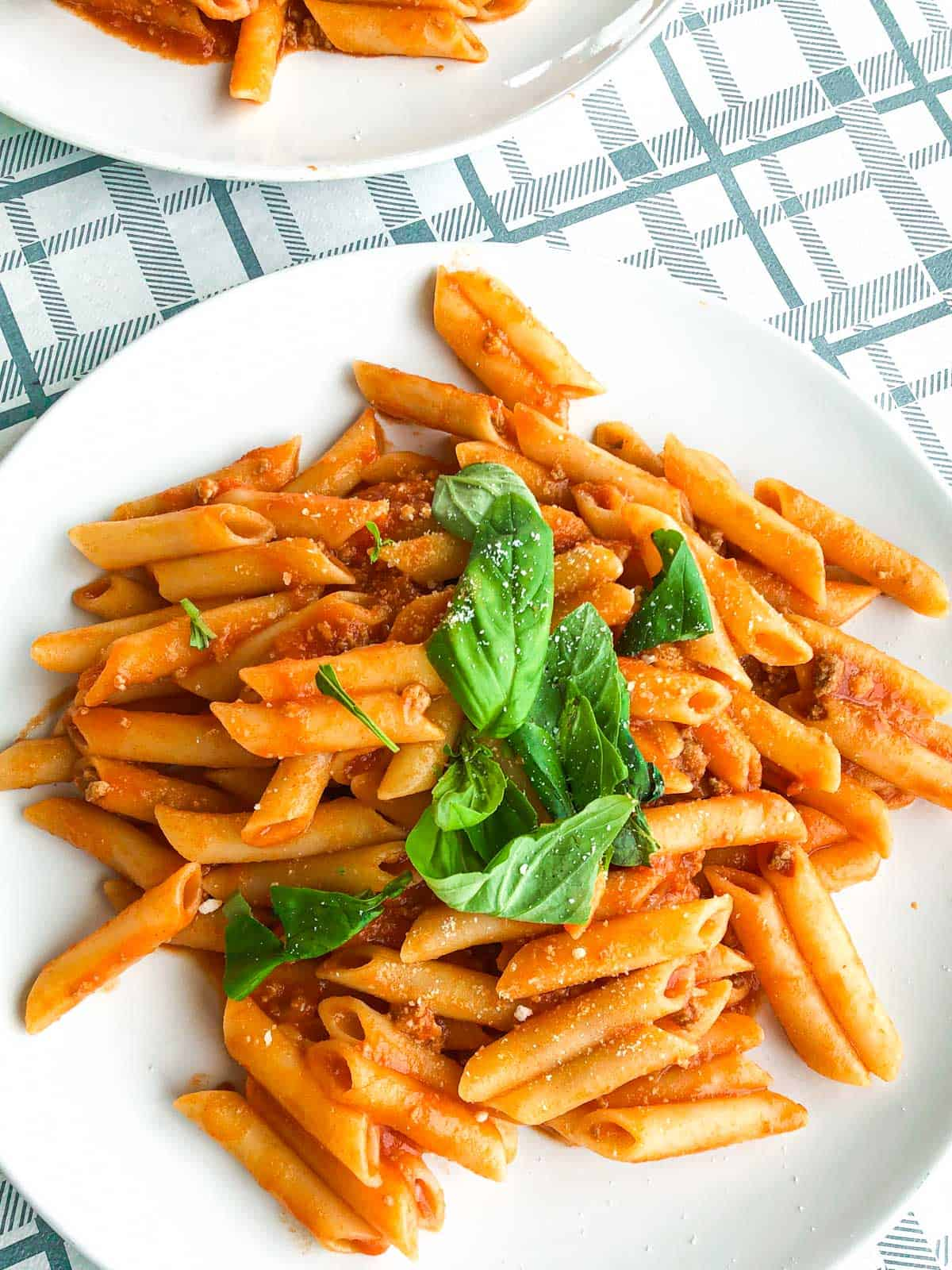 Penne ragu pasta on a white plate on a table with a checked blue and white tablecloth