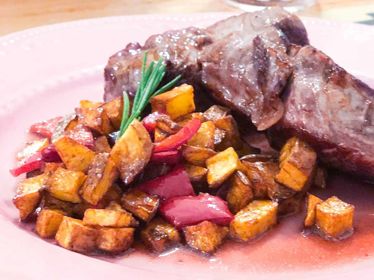 Fillet of beef with small diced roast potatoes with peppers and a spring of rosemary on a pink plate