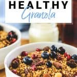Bowl of chunky nut healthy granola topped with blueberries and pomegranate seeds
