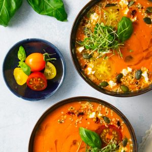 Two bowls of homemade tomato soup topped with herbs and seeds