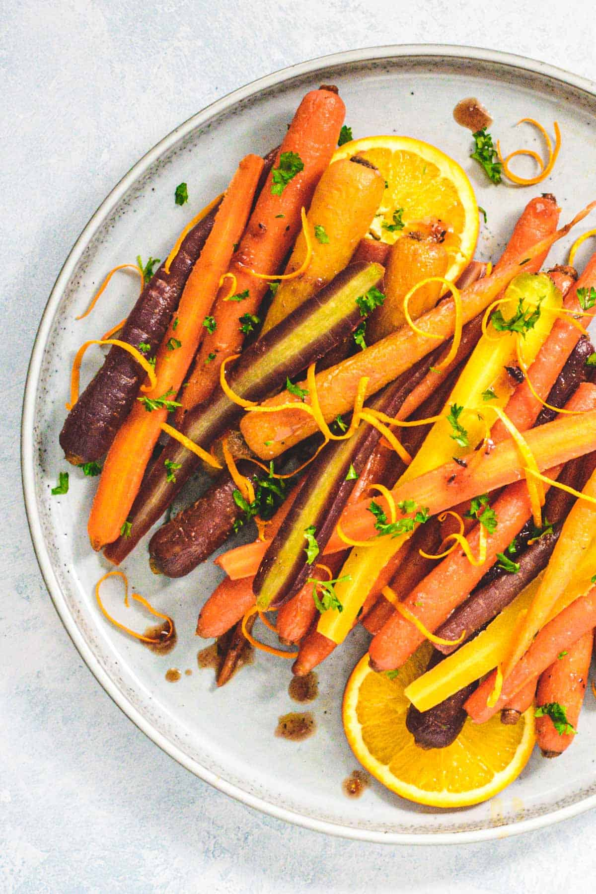 Honey glazed carrots with orange and cumin on plate with sliced oranges and orange zest