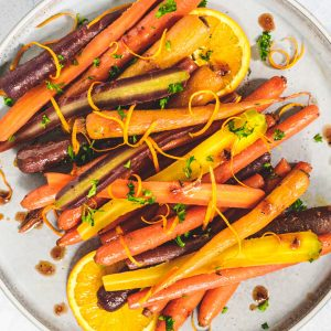Heirloom carrots on plate with sliced oranges