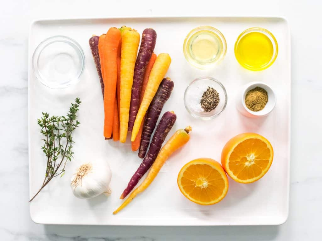honey glazed carrots ingredients laid out on rectangle white plate