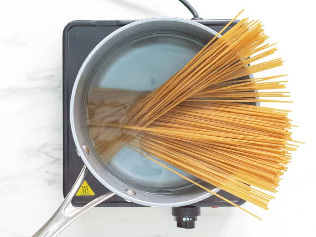 Dried spaghetti in a saucepan of boiling water