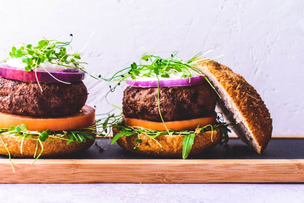 Two homemade burgers on a slate and wooden board
