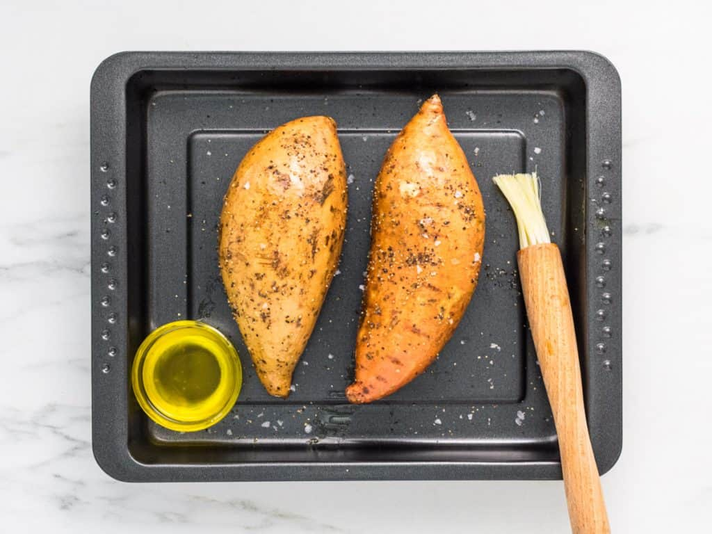 Two raw sweet potato jackets on a baking tray brushed with olive oil