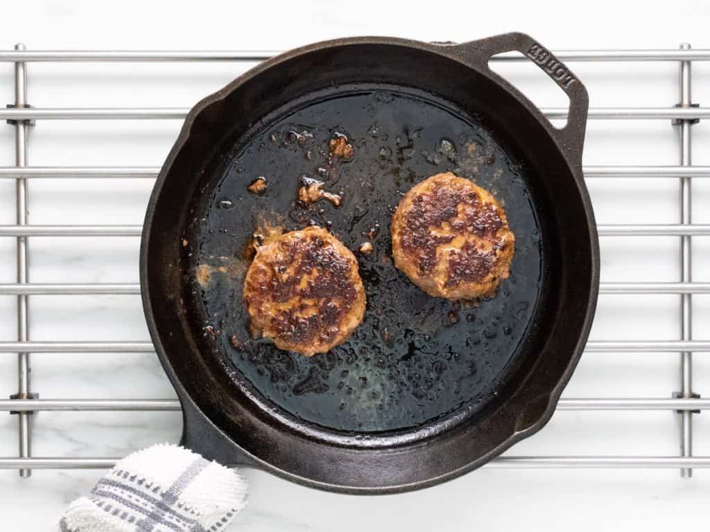 Two cooked homemade burgers in skillet