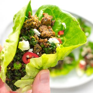 close up shot of hand holding a spiced lamb lettuce wrap