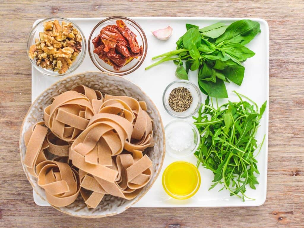 Ingredients for whole wheat pappardelle with sundried tomatoes, rocket and walnuts on a large, white rectangular plate