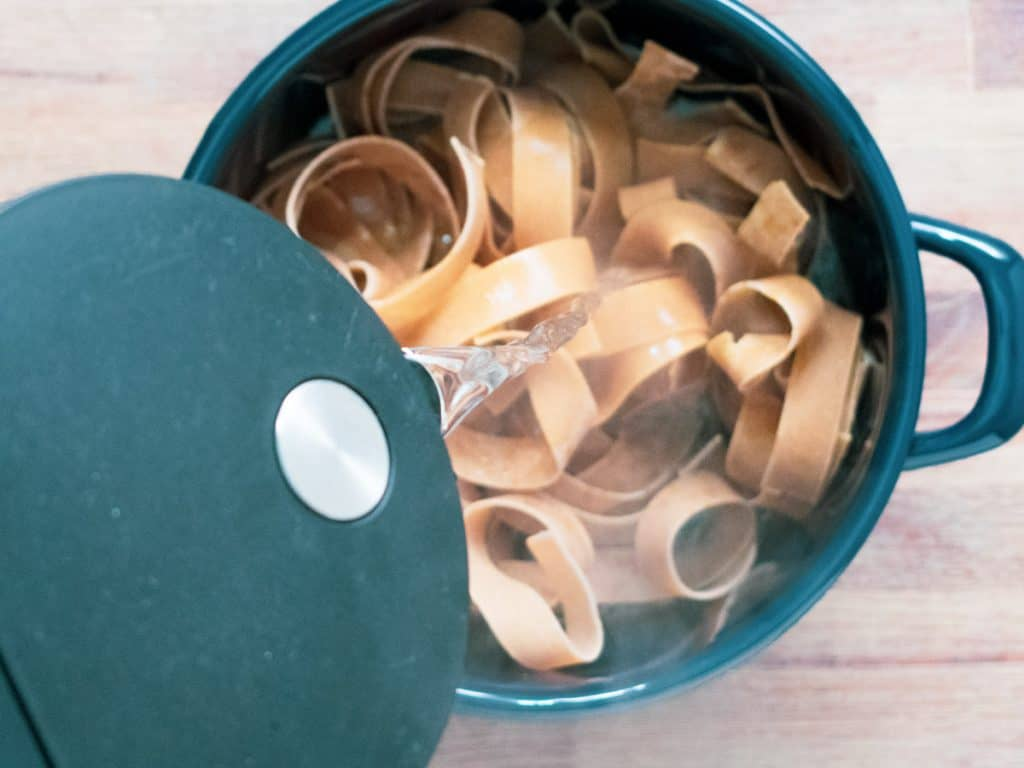 Boiling water being poured into a saucepan with whole wheat pappardelle