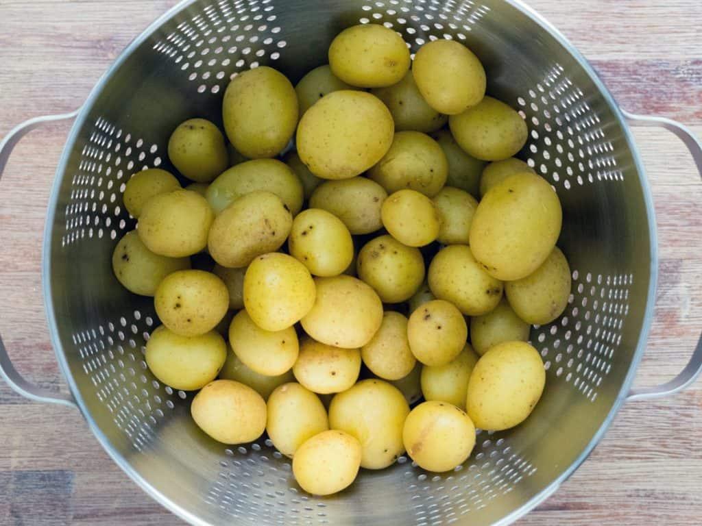 Par-boiled new potatoes draining in colander