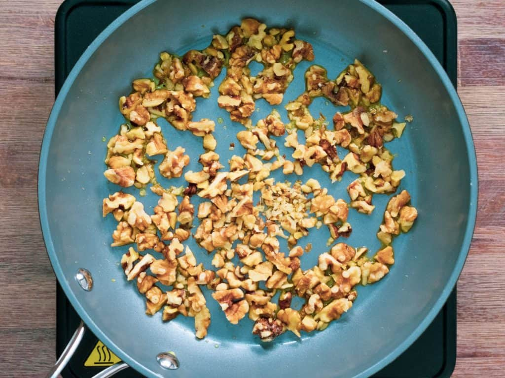 Walnuts frying in pan