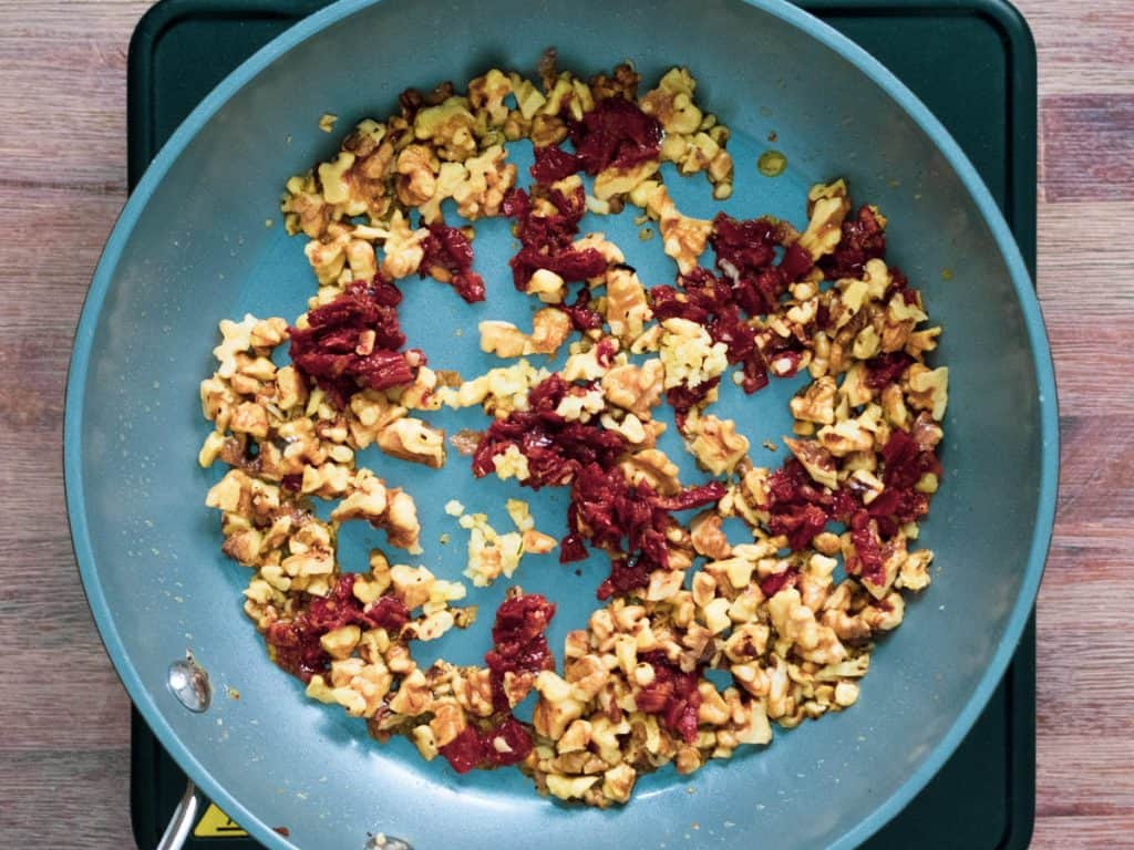 Sundried tomatoes and walnuts frying in a pan