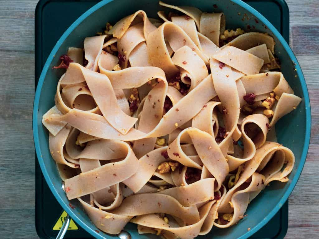 Whole wheat pappardelle in frying pan with sundried tomatoes and chopped walnuts