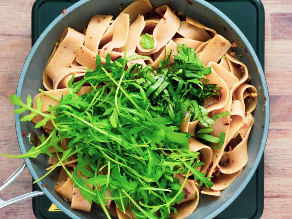 Whole wheat pappardelle in a frying pan with sundried tomatoes, rocket, basil and walnuts