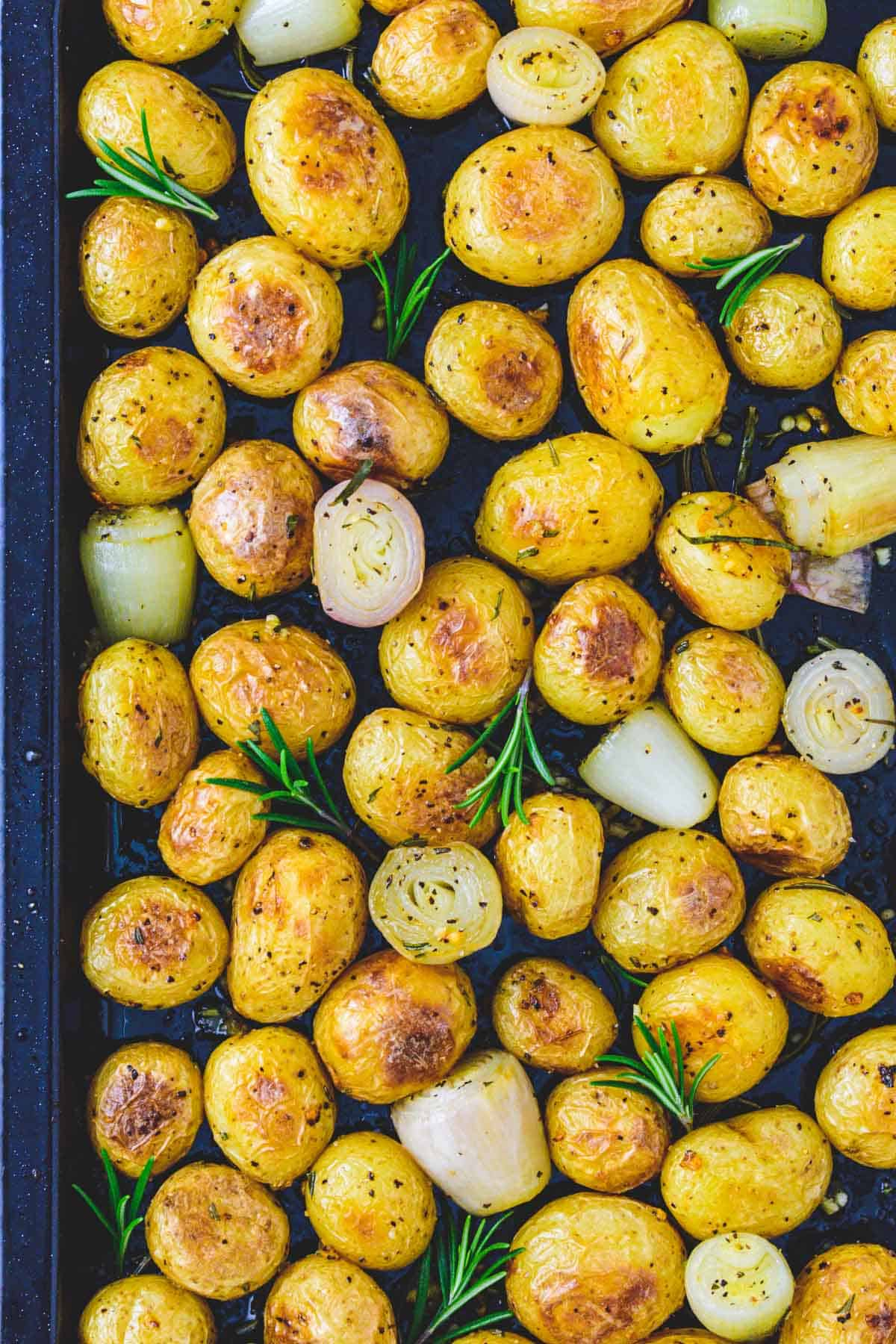 Roasted new potatoes with garlic, rosemary and shallots on baking tray
