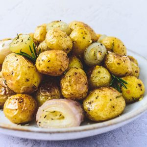 Roasted new potatoes with garlic, rosemary and shallots in a large bowl