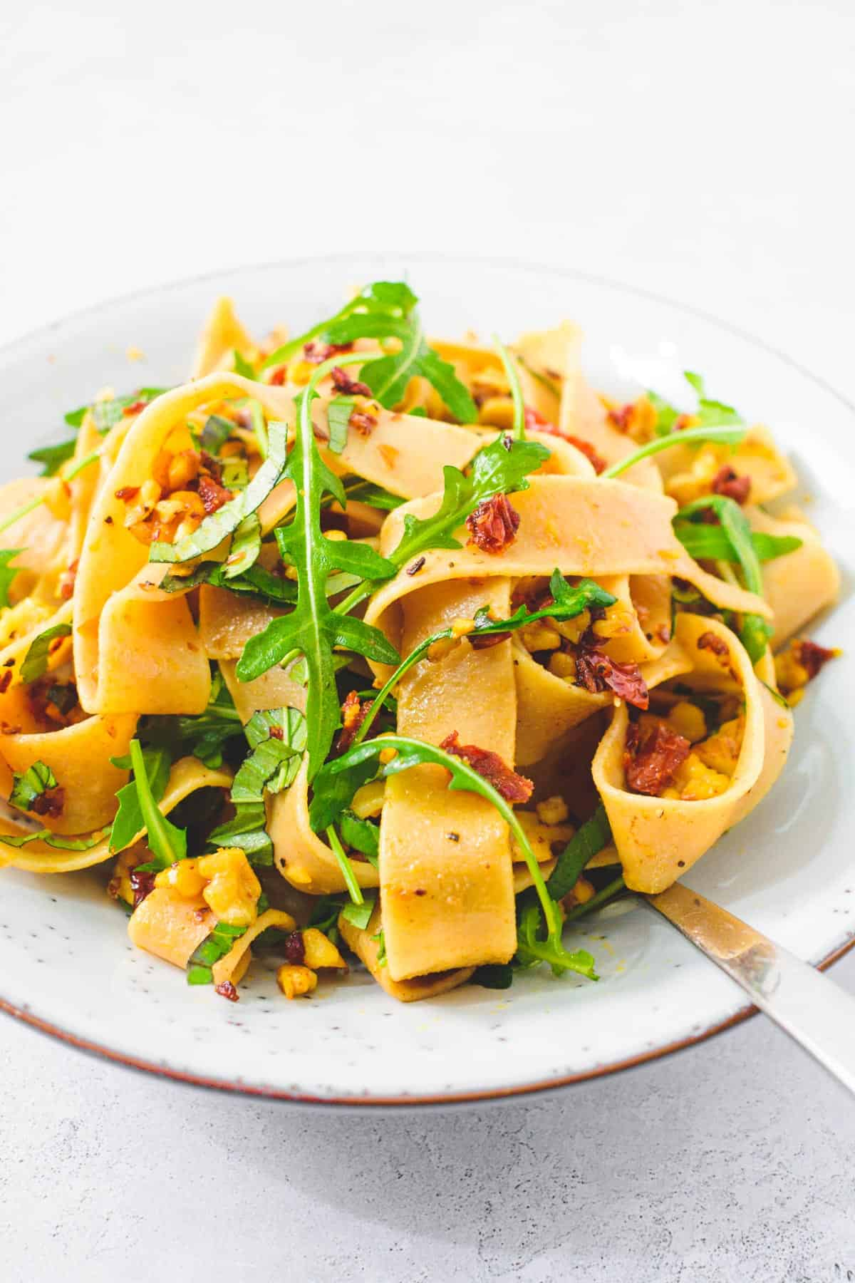 Whole wheat pappardelle with sundried tomatoes, rocket & walnuts in a pasta bowl, with fork.