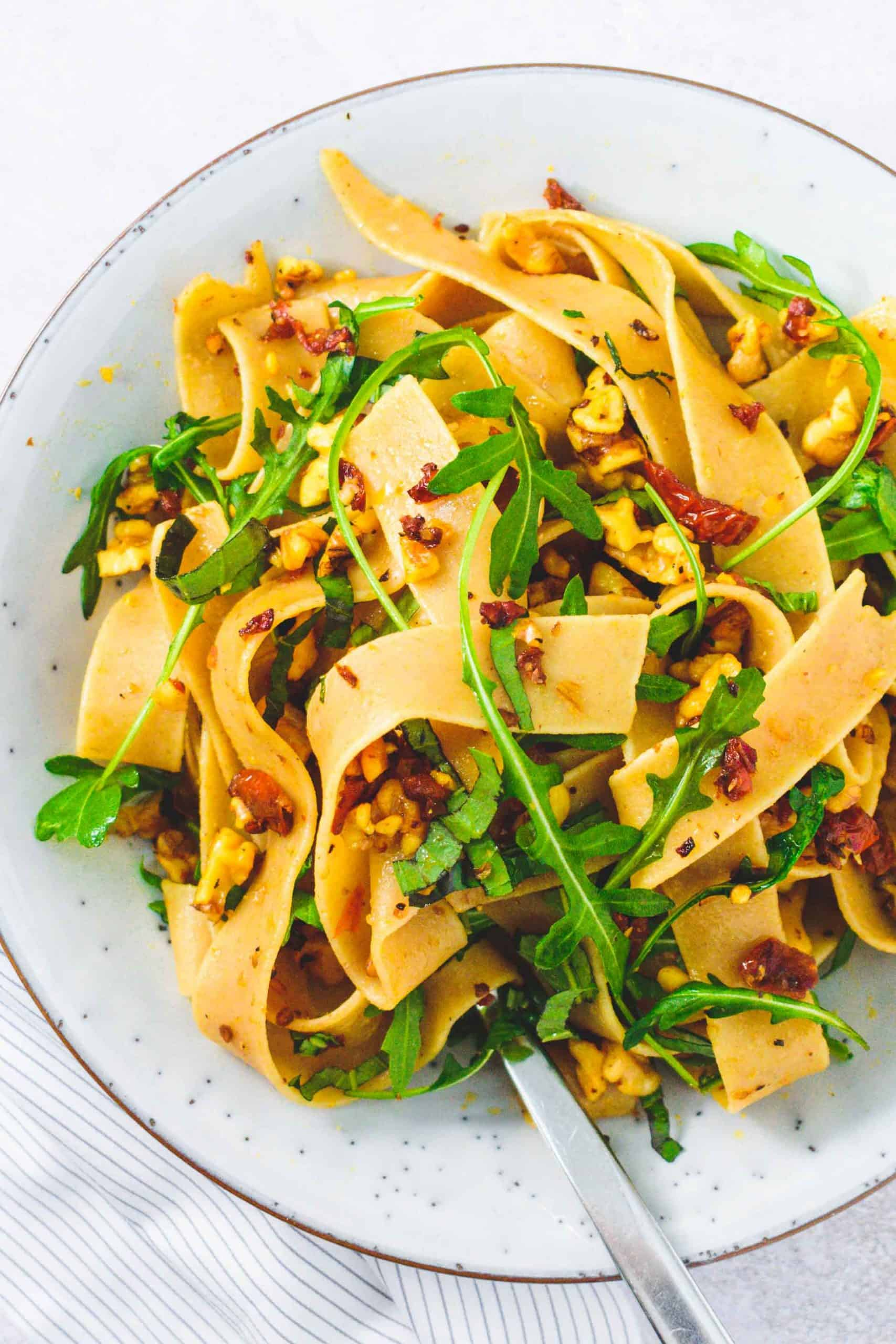 Whole wheat pappardelle with sundried tomatoes, rocket and walnuts in a round pasta bowl with fork