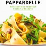 Close up image of whole wheat pappardelle with sundried tomatoes, rocket and walnuts