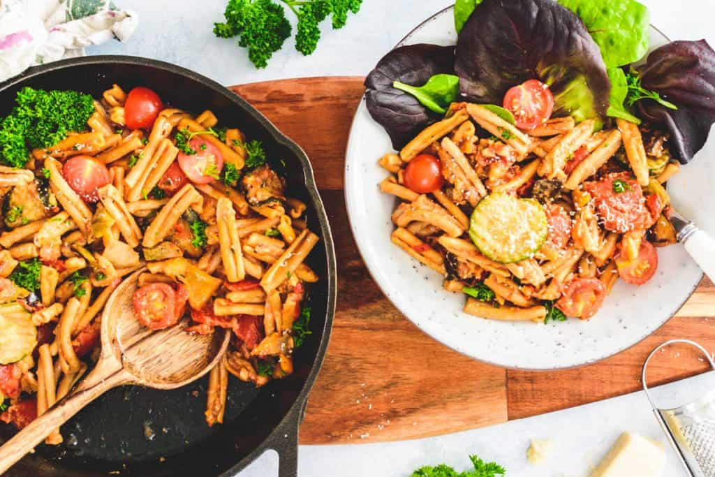 Skillet of Mediterranean Vegetable Pasta with a portion in a pasta bowl