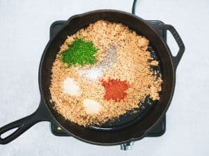 Uncooked wholemeal breadcrumbs in skillet with parsley, spices and seasonings