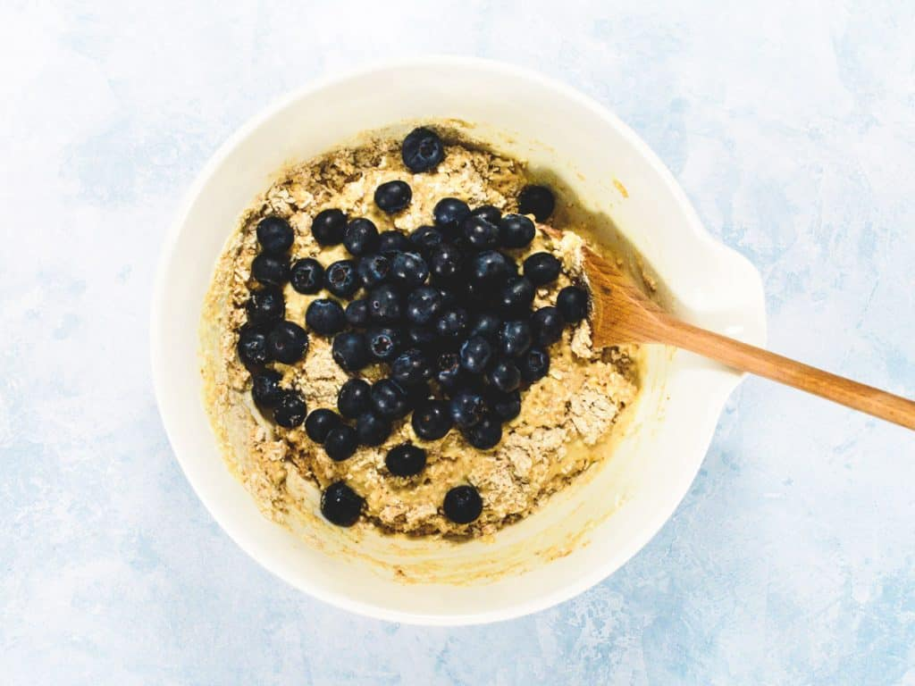 Muffin batter in a white bowl with blueberries