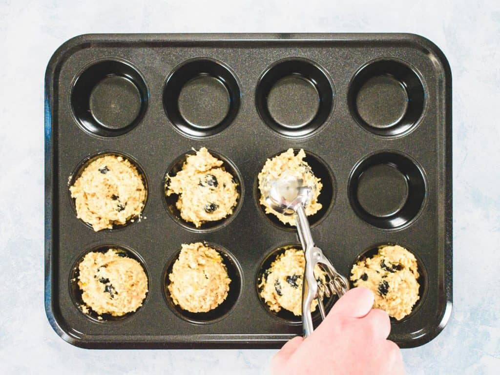 Hand scooping muffin batter into a muffin tray with an ice cream scoop