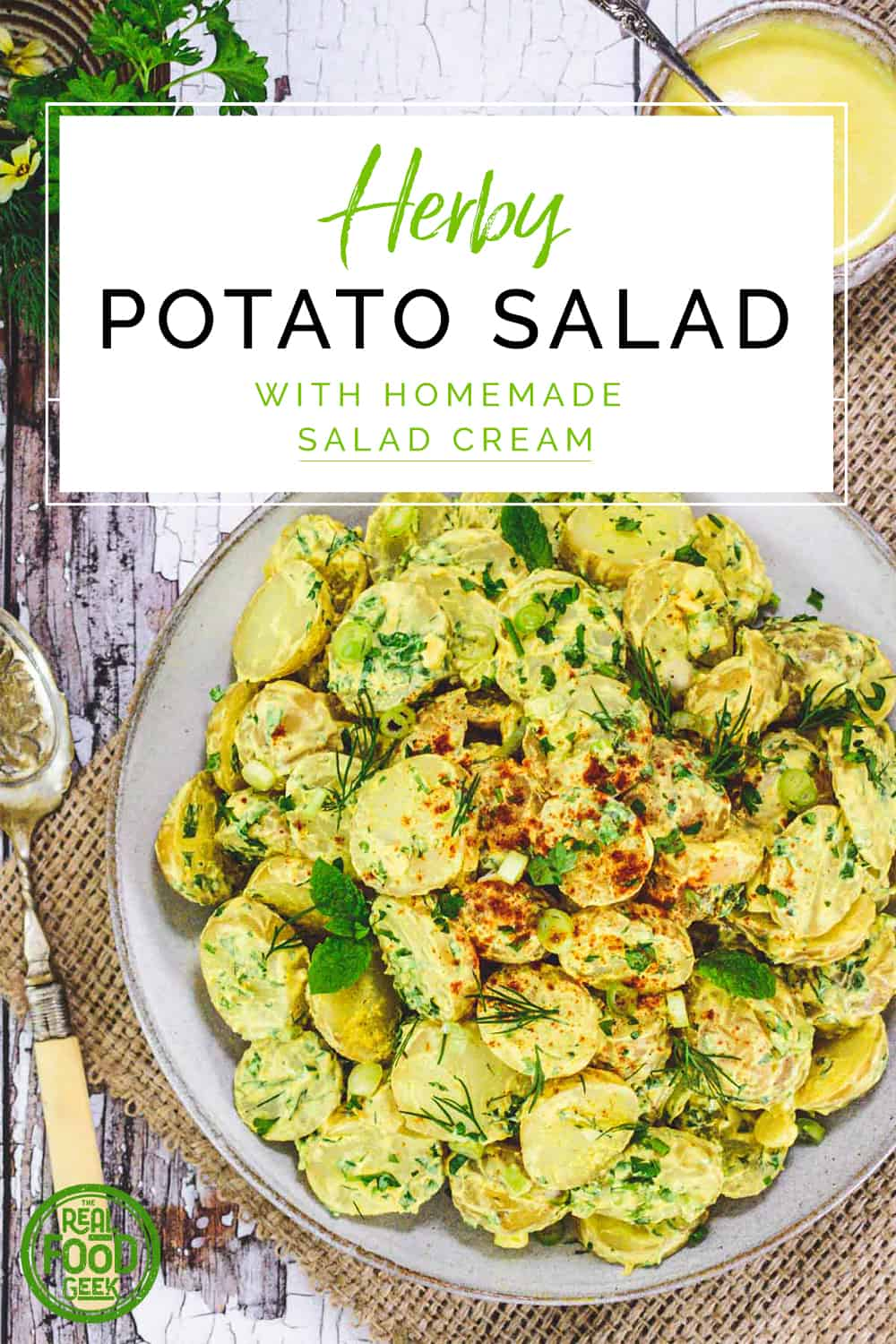 Bowl of herby potato salad with a small pot of salad cream and old spoon and herbs