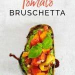 A single tomato bruschetta drizzled with balsamic glaze on a grey background