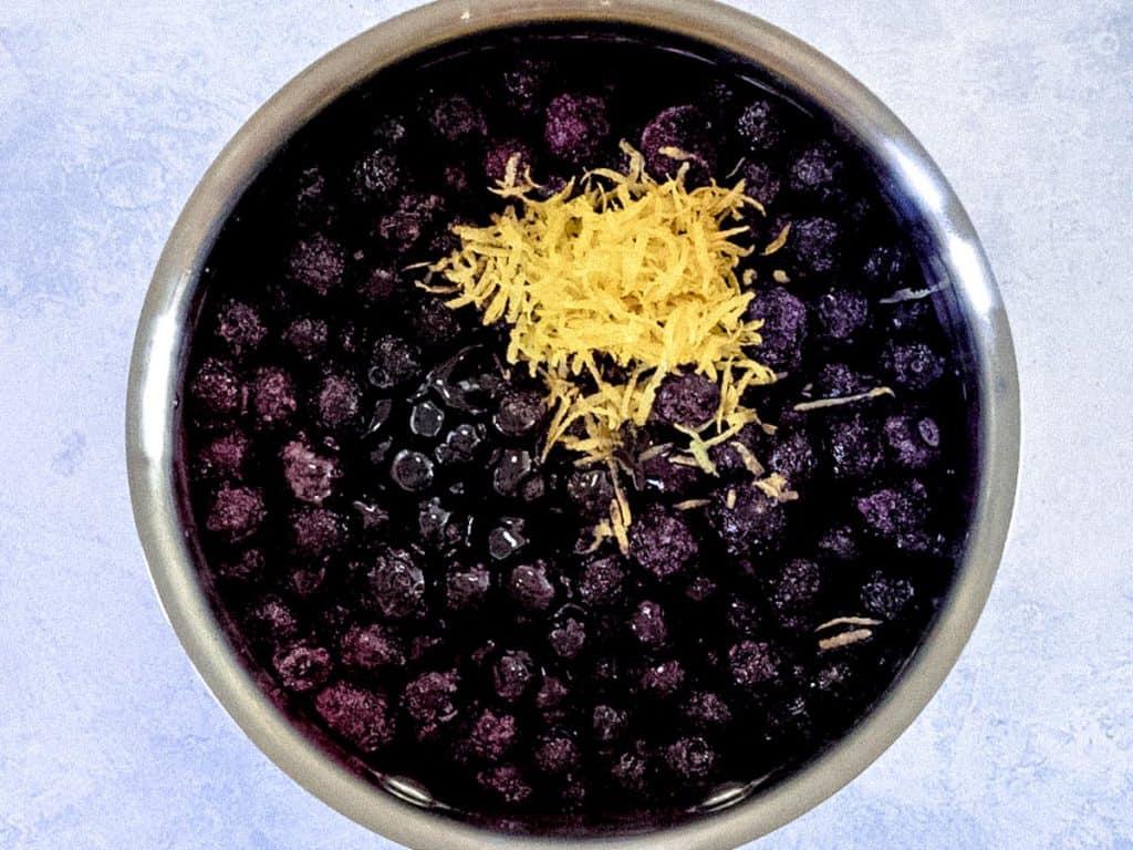 Saucepan with frozen blueberries and lemon zest