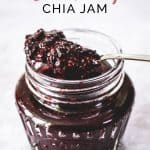 Open jar of blueberry chia jam with spoonful of chia jam resting on top