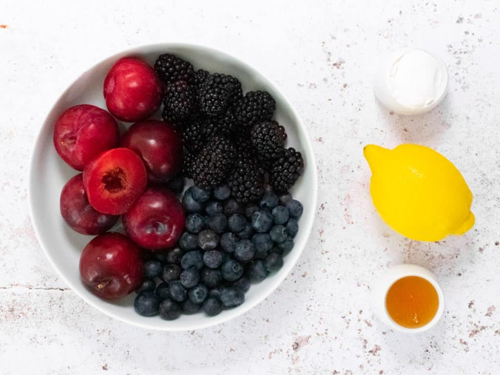 Bowl of lemons, blackberries and blueberries with a lemon, honey and tapioca to the side