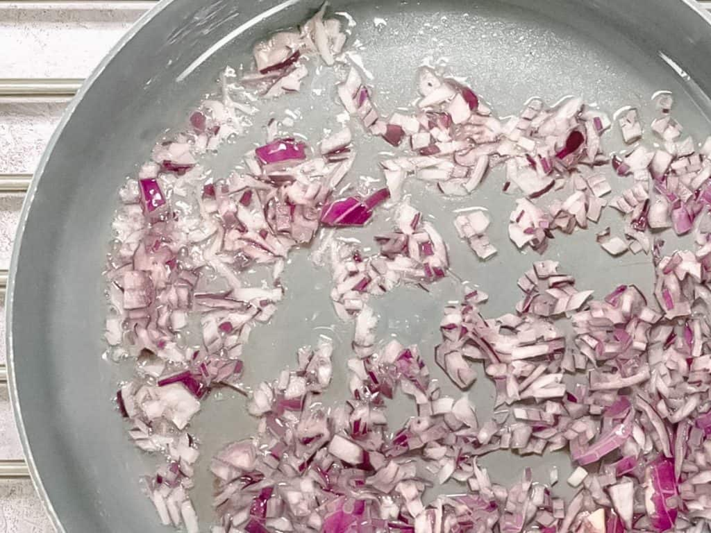 Red onions sautéing in pan