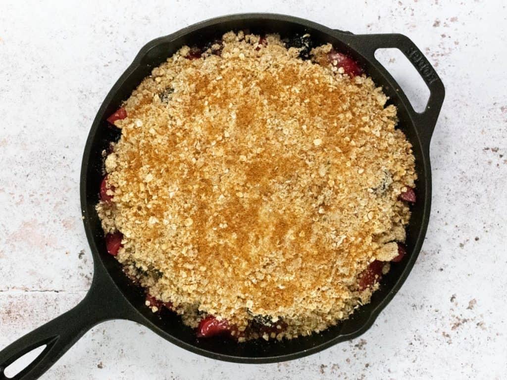 Plum berry crisp in cast iron skillet before baking