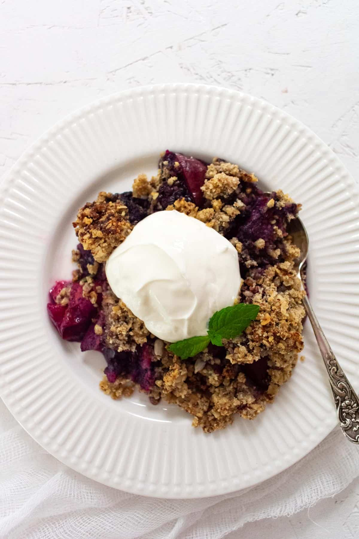 Portion of plum berry crisp on white plate topped with greek yogurt