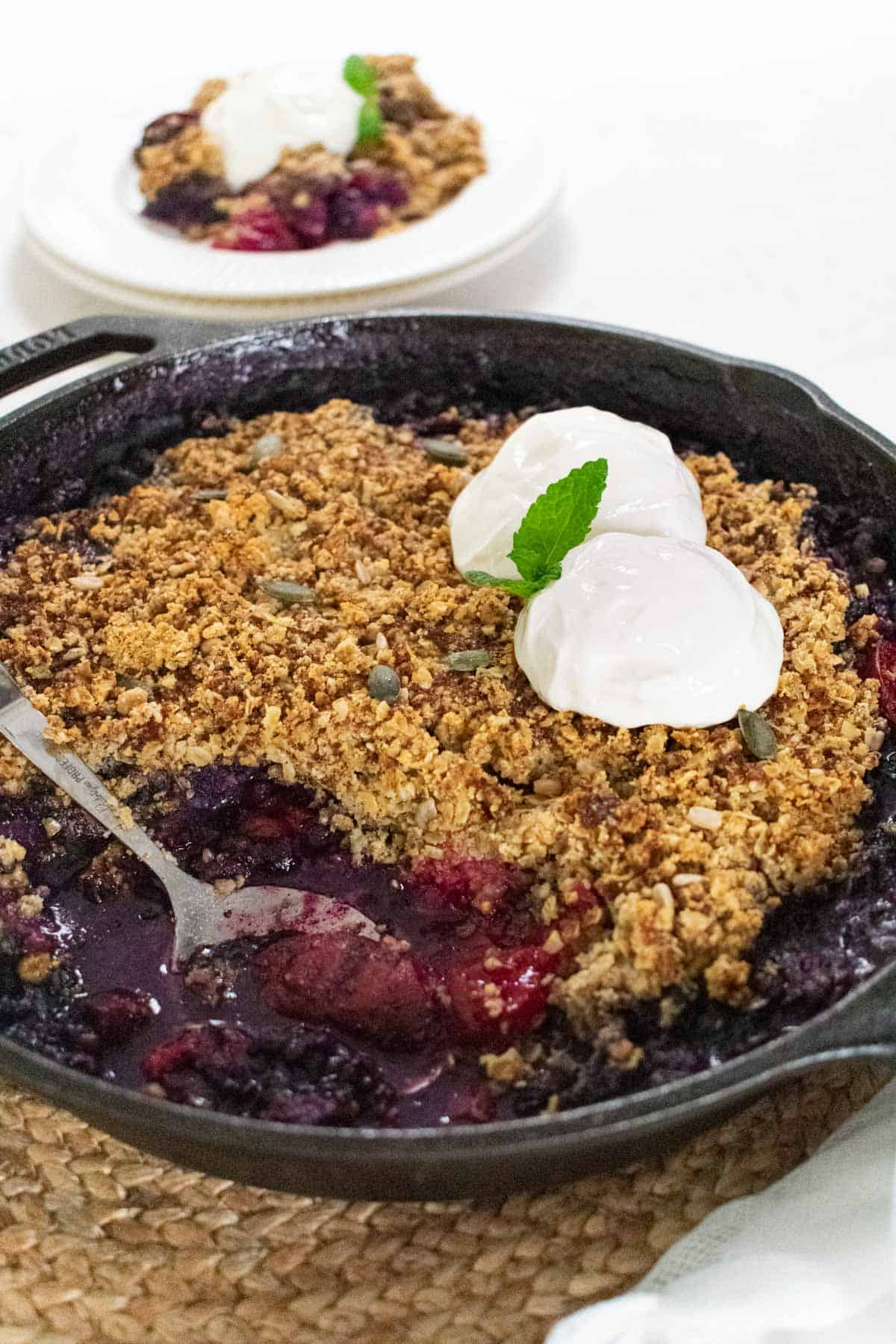 Skillet of plum berry crisp and a portion dished out on white plate