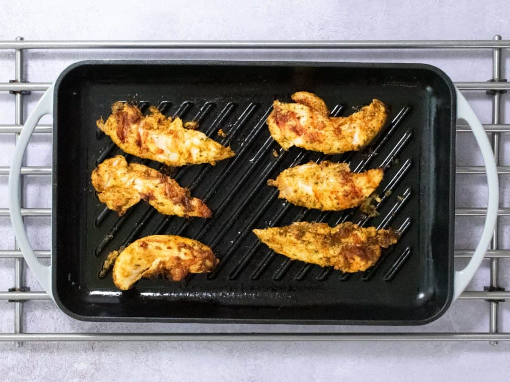 Chicken tikka pieces on grill pan