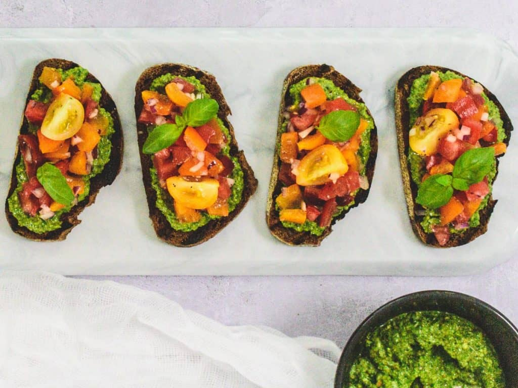 Slice of brown crusty bread with a spread of pesto, piled up with chopped tomatoes, red onions and basil.