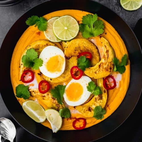 Curried Chickpea and Roasted Pumpkin Soup in a pan on a black background, surrounded with soup spoons, slices of lime and chilli and soup bowls